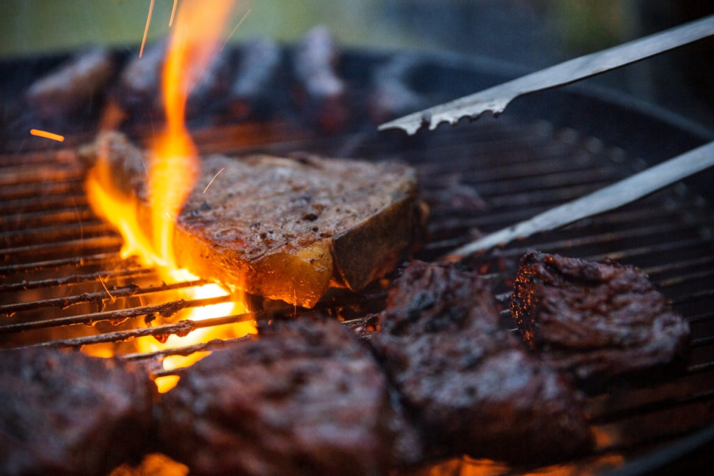 Flame grilled steaks being flipped on barbecue with tongs.