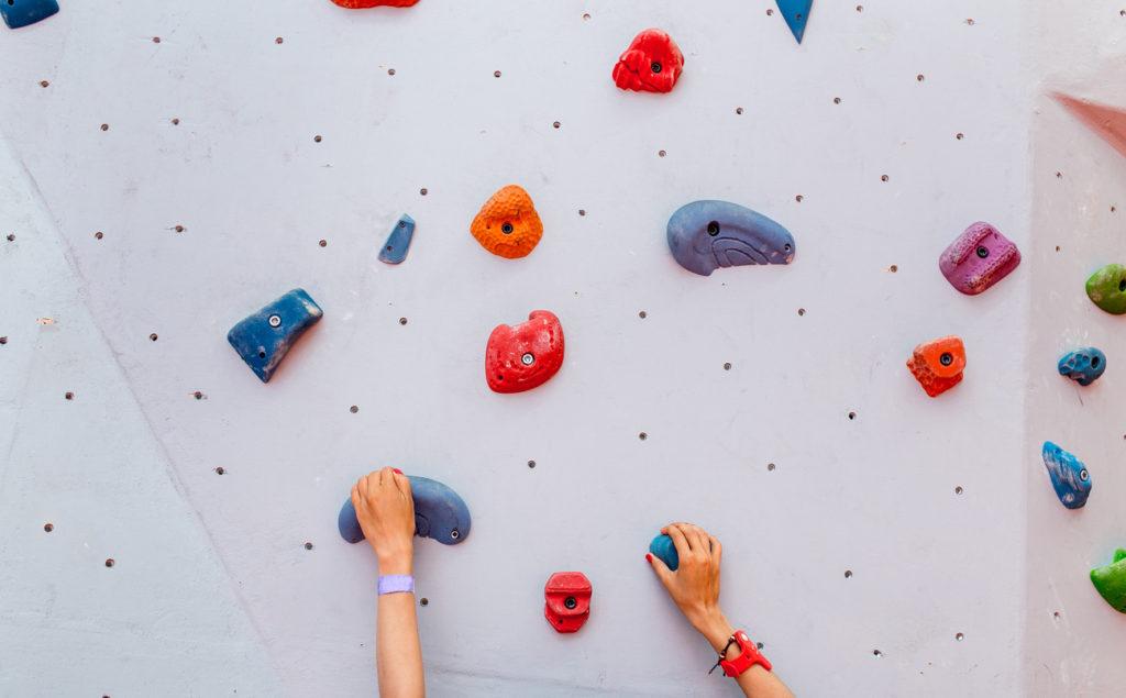 Woman climbing up a rock climbing wall