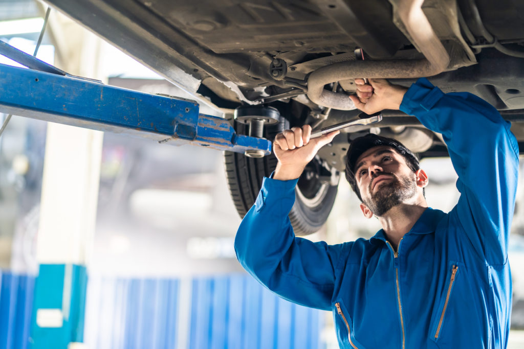 Automotive mechanic man use tool to tighten and replace damaged or broken part