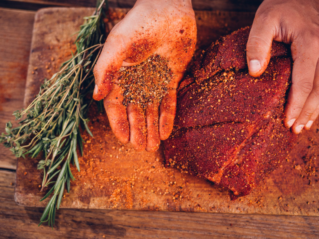 Hand rubbing a spice rub on meat