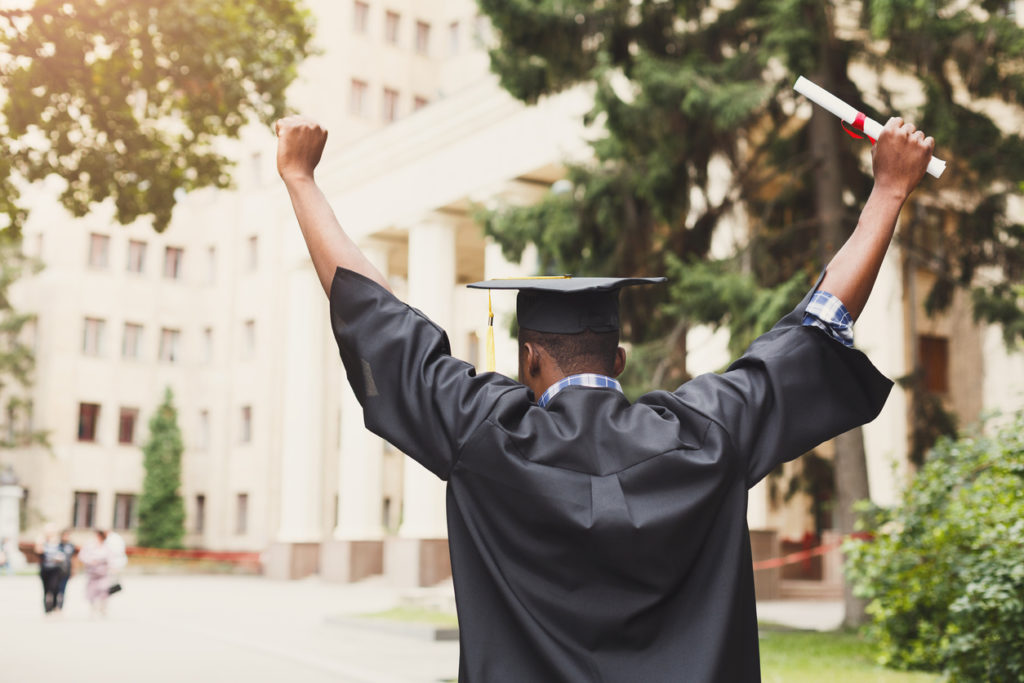 Excited graduate holding diploma in the air